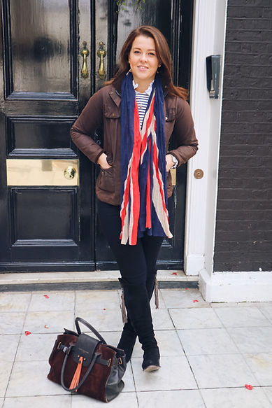 Woman standing in a doorway wearing a waxed jacket, union jack scarf and black jeans and black fairfax and favor regina boots