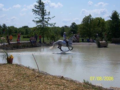 Horse running through a water hazard on an eventing course