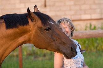 head shot horse and blond woman blurred
