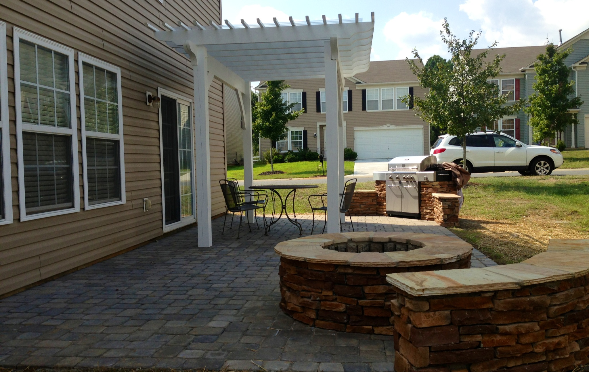 paver-patio-with-ledge-stone-fire-pit-and-sitting-wall-and-a-wood-pergola-with-an-outdoor-kitchen-in