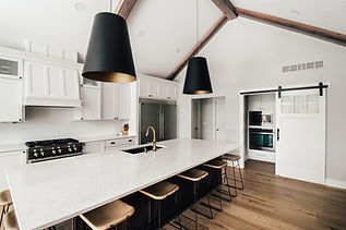 Large kitchen remodel in Ames, Iowa. White quartz countertops, large island with black pendants, barn door into pantry
