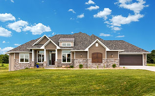 Ranch-style exterior of home in Ames, Iowa. Tan siding, earth-tone stonework, brown garage doors, tall entryway