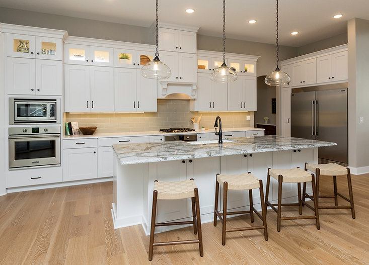 Kitchen with white cabinets, grey subway tile, 4-stool island, wall oven and microwave