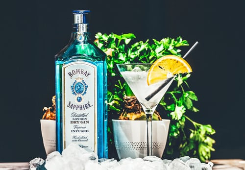 Bottle of Bombay Sapphire gin with glass of gin and garnishes