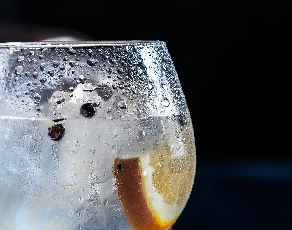 Glass of gin and tonic with lemon and juniper berries