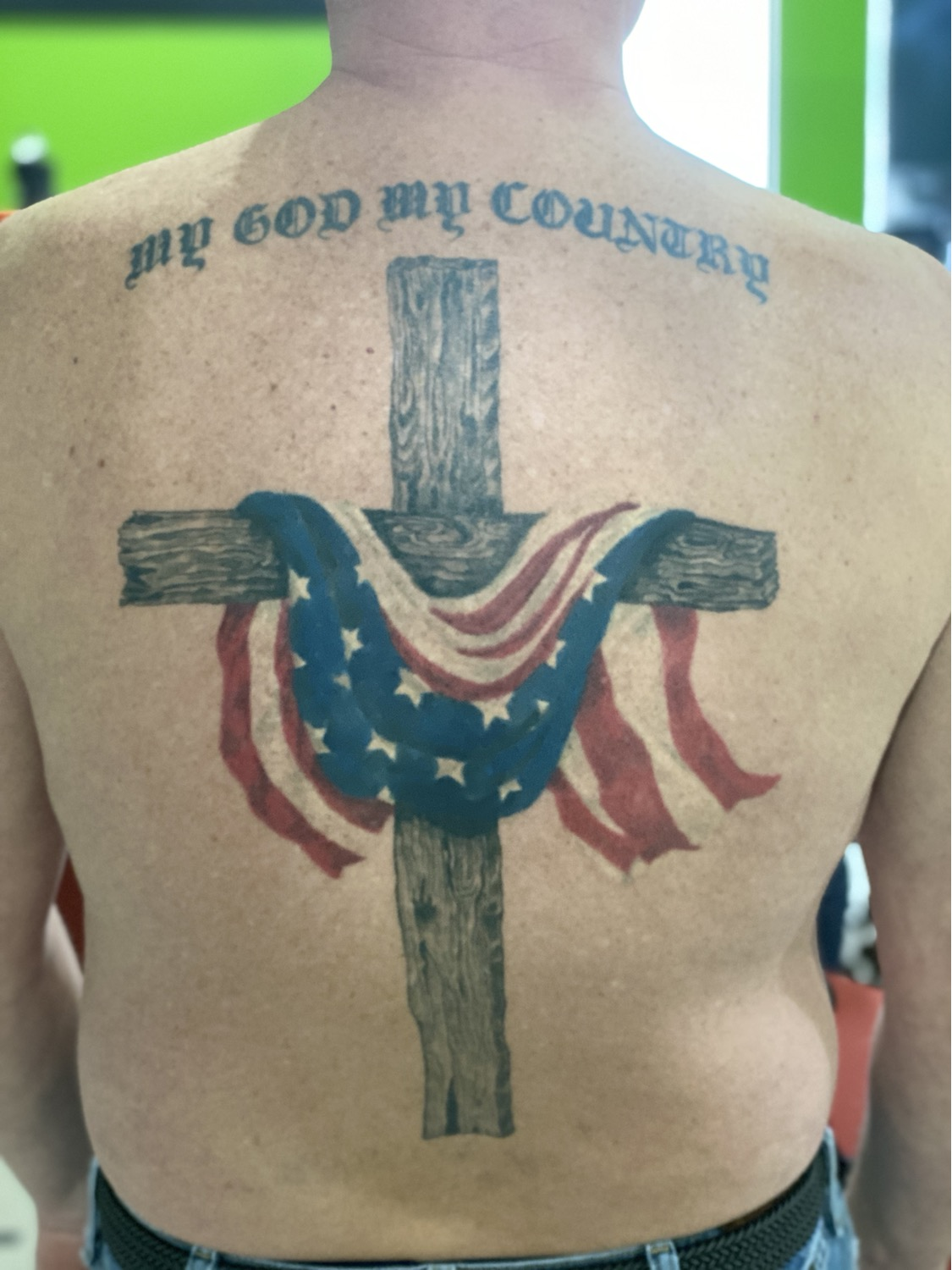 realistic black and grey cross with color flag tattoo
