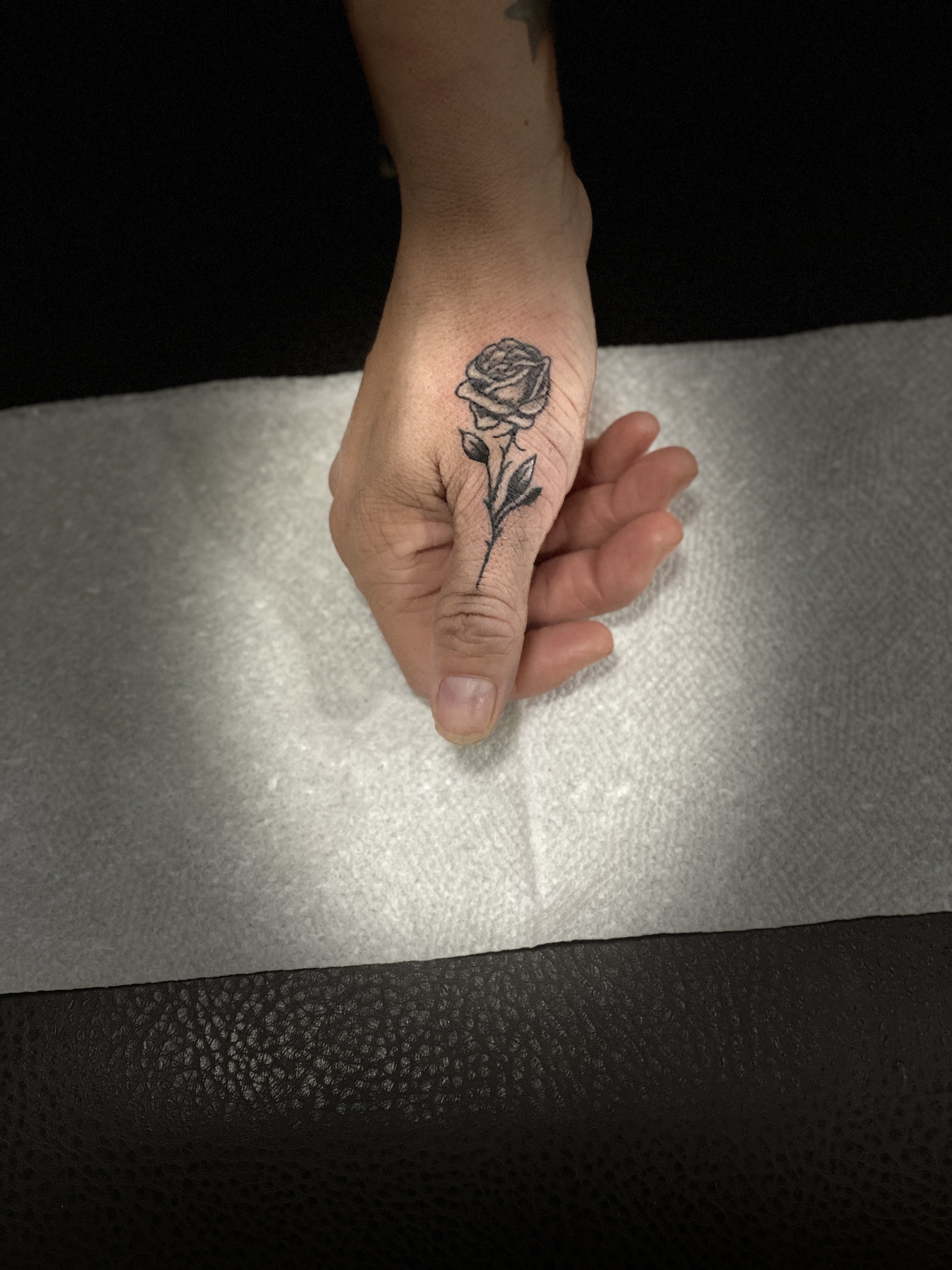 realistic black and grey rose on thumb