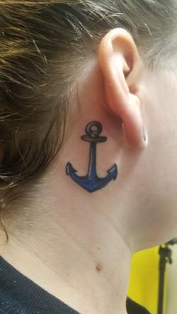 blue anchor tattoo behind the ear