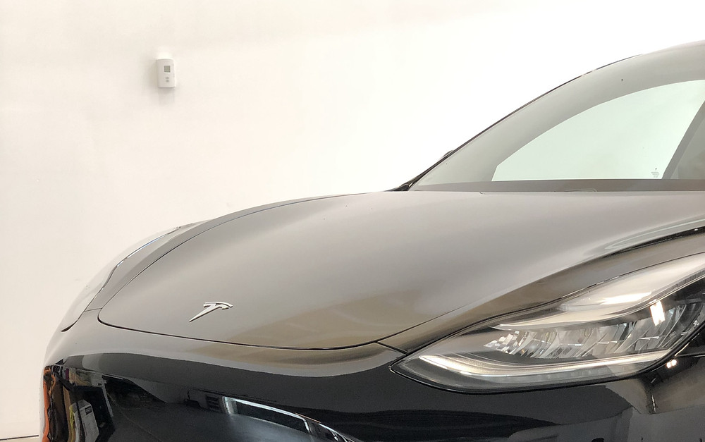 black tesla with shiny paint protection film