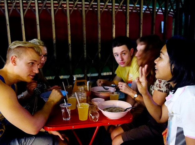 International tourists trying local street food in Bangkok
