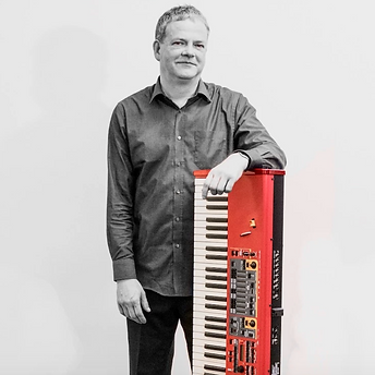 Piano teacher Steve Burholt stands next to his red Nord keyboard