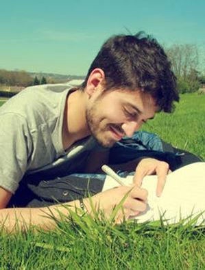 man writing laying in grass.jpeg