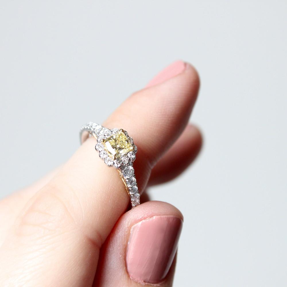 cushion cut yellow diamond ring with diamond halo on ladies hand
