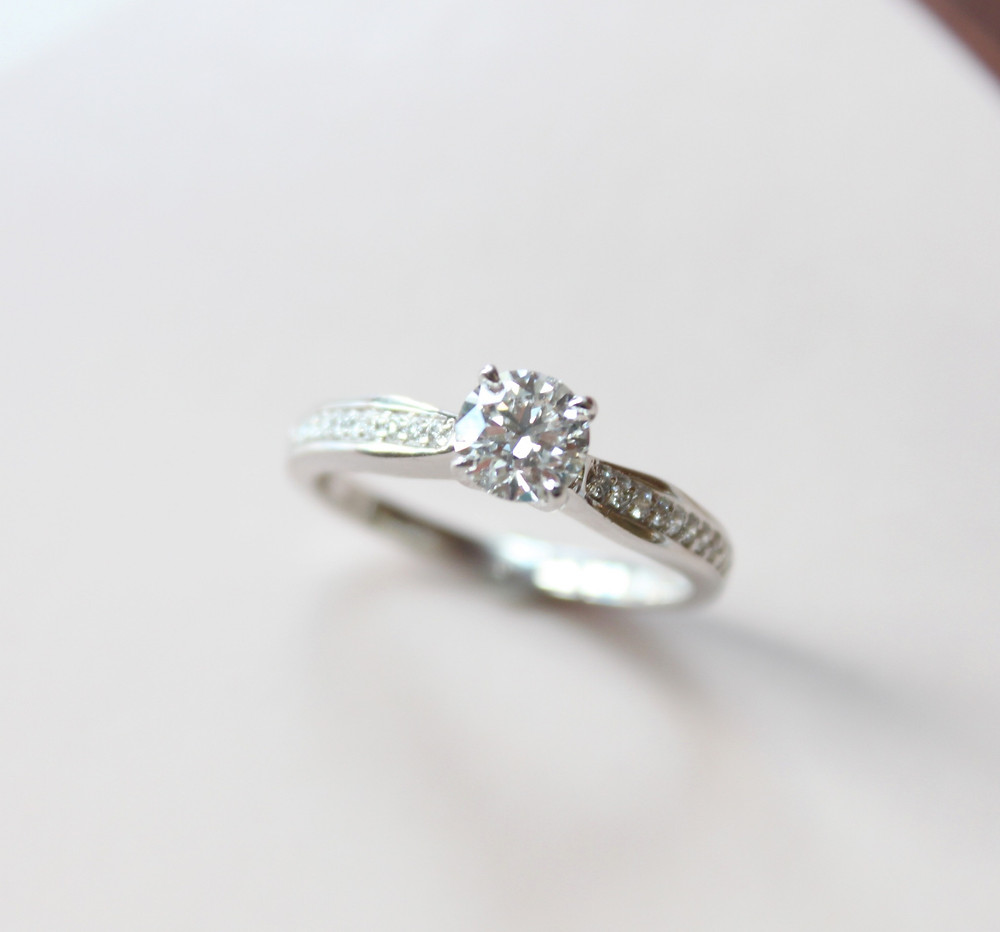 round or brilliant cut diamond engagement ring set in white gold with diamonds on the band