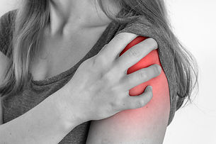 Woman with shoulder pain is holding her