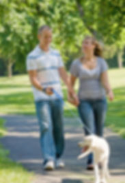 Image of happy couple walking their dog