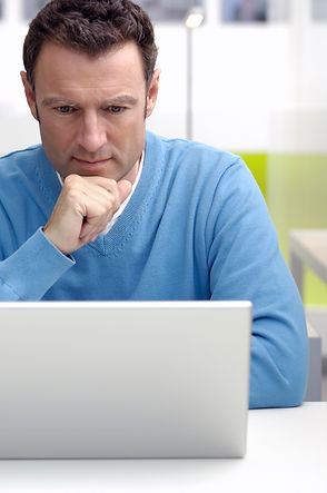 Image of a man with a laptop symbolizing filling out a form for therapy with Abigail Blackburn, PsyD