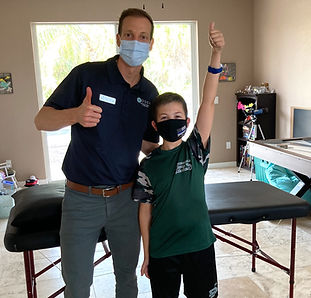 Brent with young patient at a home in mask