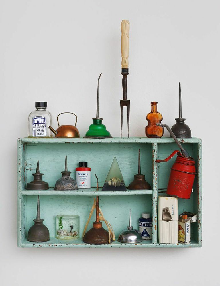 Light blue handing shelf with various metal oilers, bottles, and cannisters.