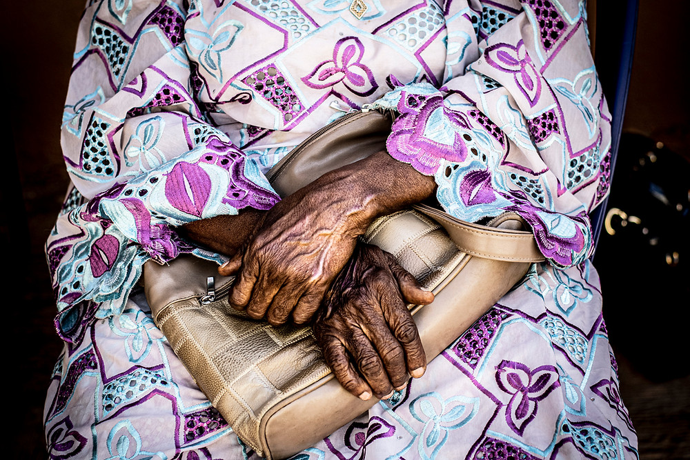 Elder woman's hands folded in her lap over her tan purse