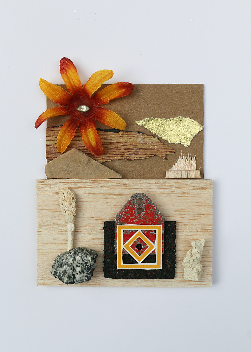 Wood collage with orange and red flower, rocks, and other shapes layered on top