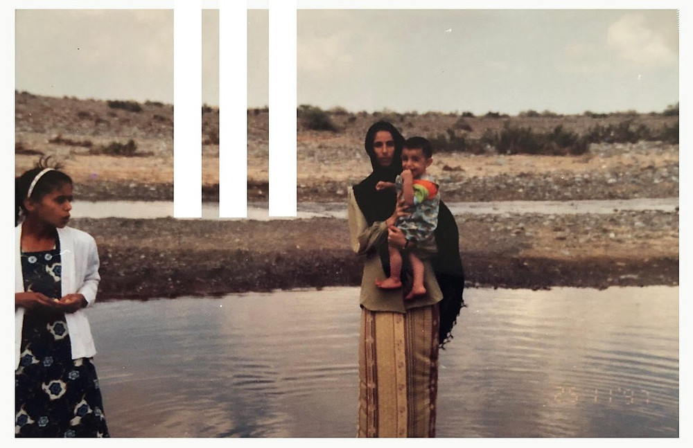 A woman stands by water with two children.