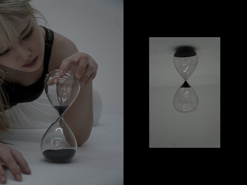 woman with blond hair holding hour glass on floor and another hour glass on ceiling
