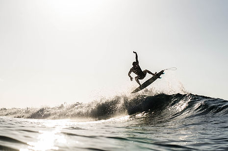 A silhouetted surfing airing on a wave b
