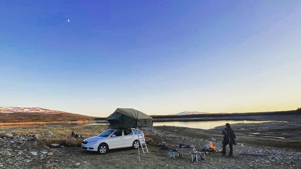 Roof top tent camping by a lake with big mountains in the background