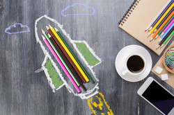 Abstract rocket ship sketch around colorful pencils on wooden desktop with other supplies, smartphon