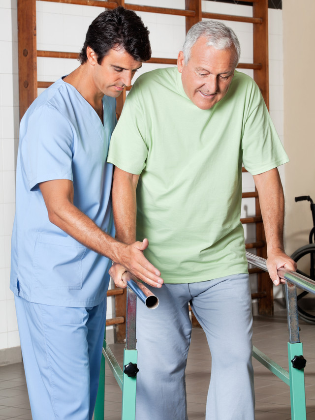 Physical therapist assisting senior man