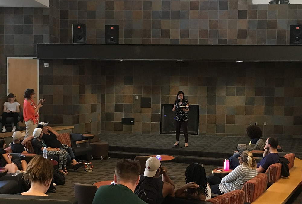 Nambo reading aloud her poem to an audience