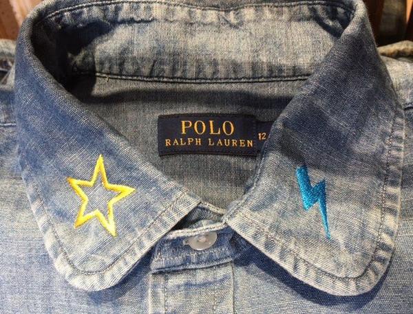 Embroidering symbols onto denim shirts for Ralp Lauren.