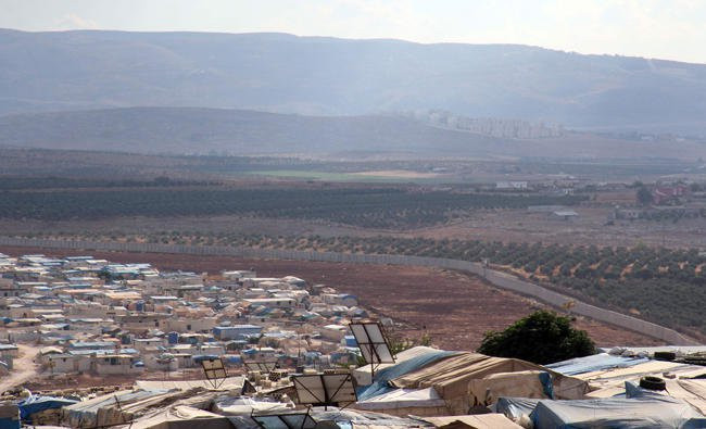 A picture taken on October 11, 2017, from the Syrian village of Atme in the northwestern province of Idlib shows a refugee camp (bottom) next to a three-meter high fortification built by the Turkish government along its border.