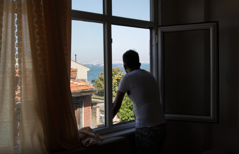 In Istanbul, Turkey, Ahmed Stanekzai (not his real name) looks out over the Marmara sea from his apartment in Istanbul. (Photograph by Adnan R. Khan)