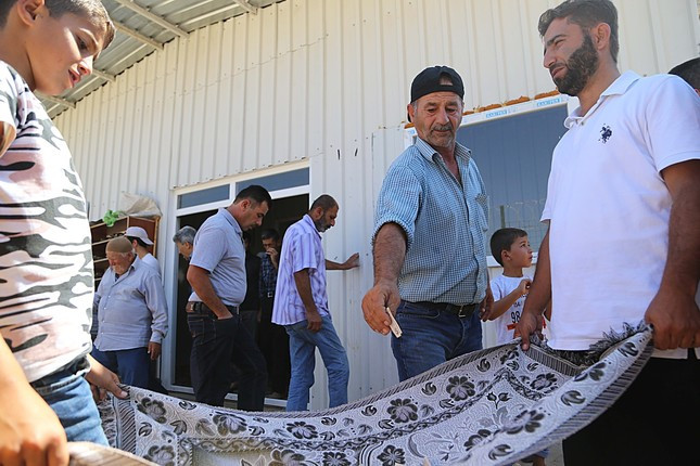 Refugees drop their donations for Rohingya Muslims on a rug after they leave the mosque at the camp in southern city of Hatay.