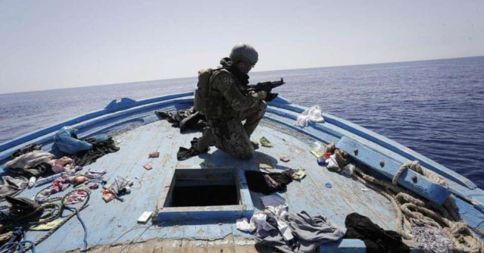A soldier secures the deck of an abandoned boat during an Italian Navy operation 'Mare Nostrum' in the Mediterranean Sea, 2015