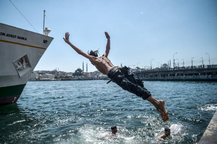 A Syrian refugee youth dives into the Bosphorus during a warm summer day on August 13, 2017 at Karakoy Port in the Turkish city of Istanbul