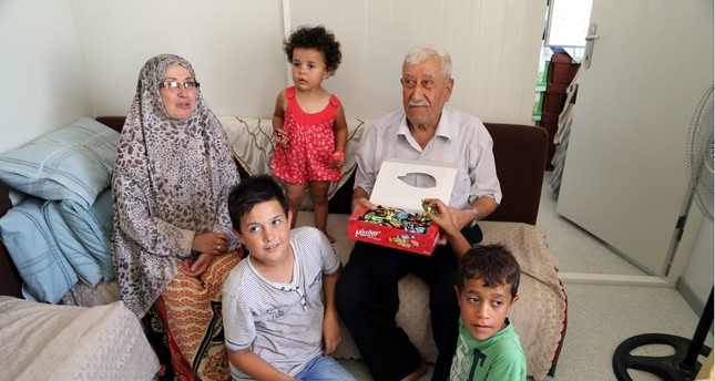 Muhammad Hasan Karrimo and his wife Melek hand out candy to their grandchildren who are among the few relatives they have in Turkey