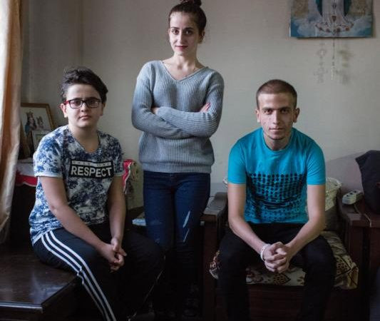 Yusuf, 12, Reeta, 17, and Fadi, 19, pose Oct. 13 at their home in Istanbul. They arrived in Turkey from Iraq more than two years ago and have not attended a formal school