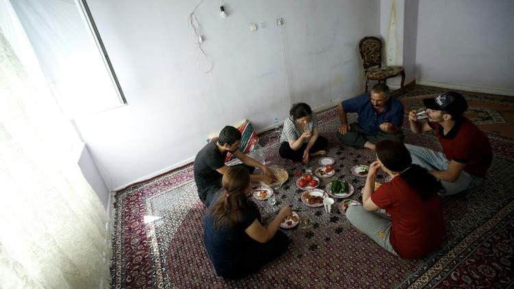 The Moradi family gathers for lunch in an apartment lent by a friend