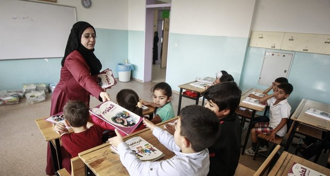 A teacher distributes textbooks to Syrian students at a school in the capital Ankara