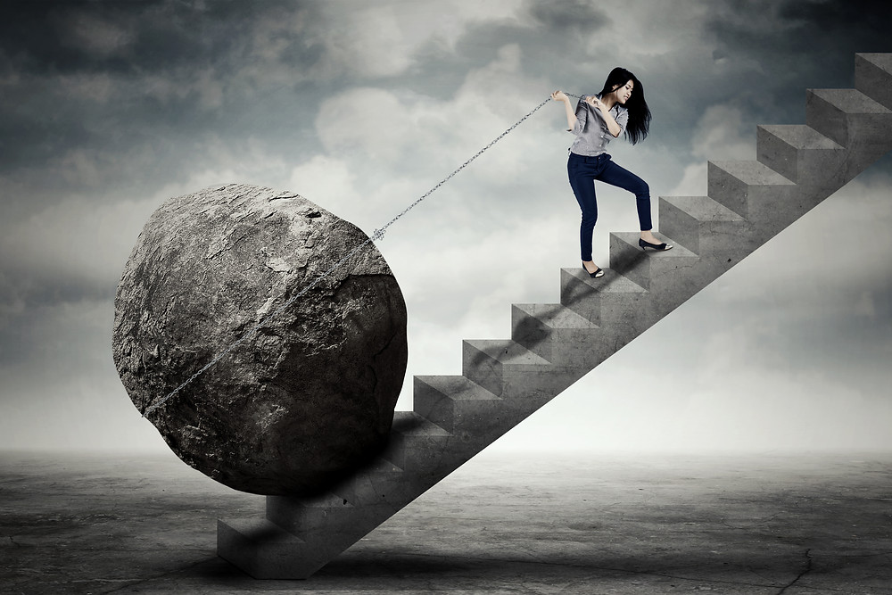 Asian young adult pulling boulder up stairs. Represents the need for counseling for young adults katy, tx 77494. Also represents the need for teen therapy katy, tx and teen counseling katy, tx 77494.