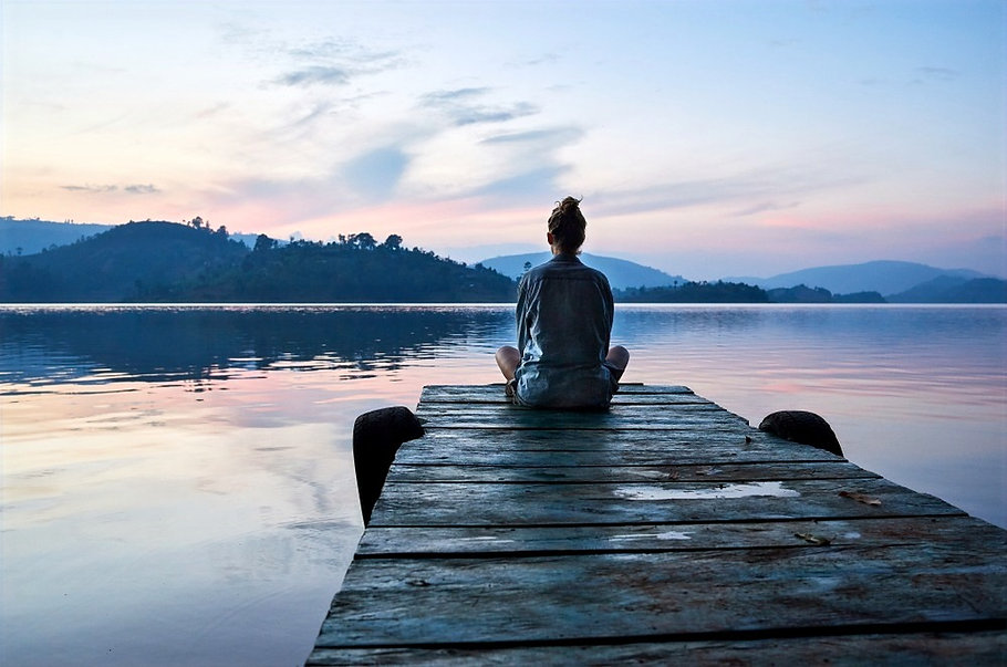Teenager sitting on a dock overlooking lake and mountains. Represents teen anxiety counseling and therapy for teen anxiety in katy texas and therapy for teen anxiety in houston texas. 77494.