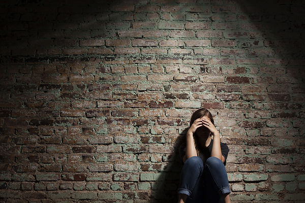 Teen girl sitting against a brick wall looking sad. Represents need for depression counseling katy texas. Also represents need for teen depression counseling houston texas. Therapist for teen depression 77493.
