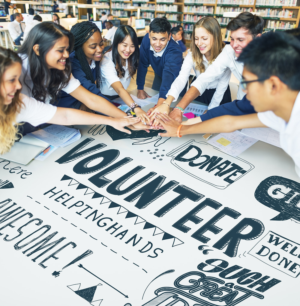 Group of teens putting their hands on top of each other over a volunteer sign. Represents the need for teen trauma therapy katy, tx and teen ptsd treatment katy, tx 77494.