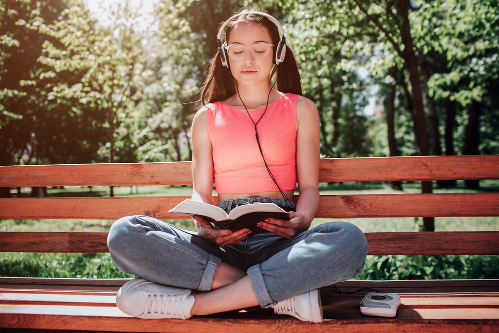 Woman sitting crossed legged on a park bench, headphones, reading a book. Represents the need for teen therapy katy, tx and teen counseling katy, tx. Also represents the need for family therapy katy, tx and family counseling katy, tx.