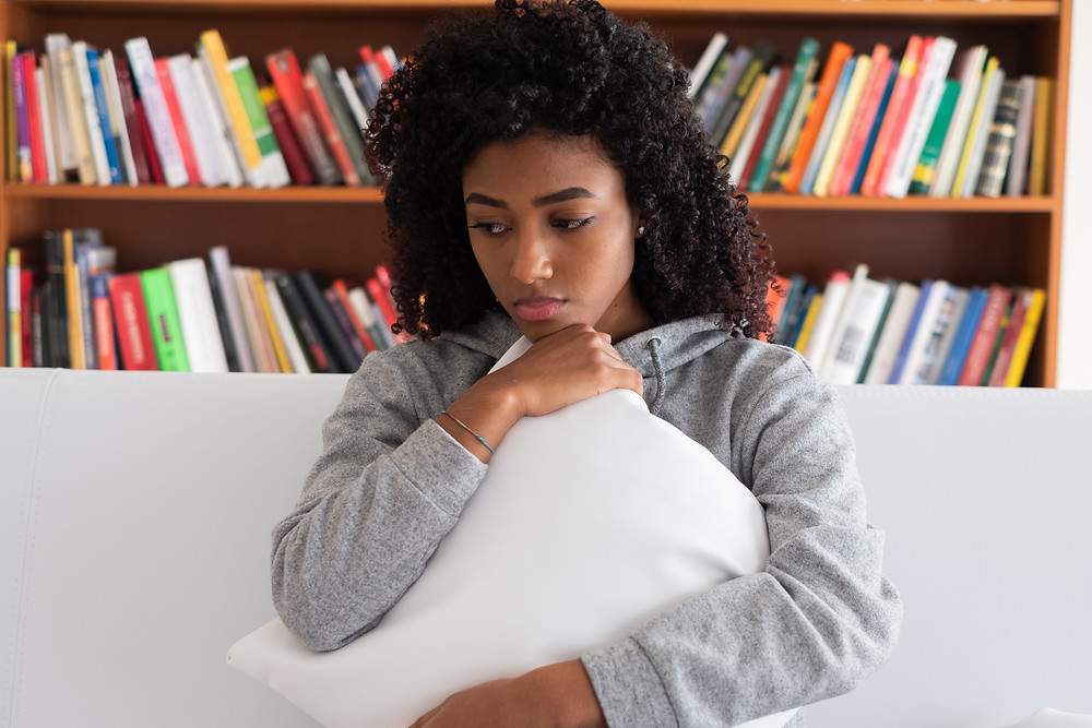 Black teen hugging pillow on couch looking sad. Represents need for teen anxiety counseling in katy tx. Also represents therapist for teen depression katy tx.