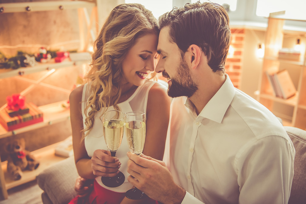 Couple with foreheads touching, smiling, holding flutes of Champaign. Represents the need for marriage counseling katy, tx 77494. Also represents the need for couples therapy katy, tx 77494.