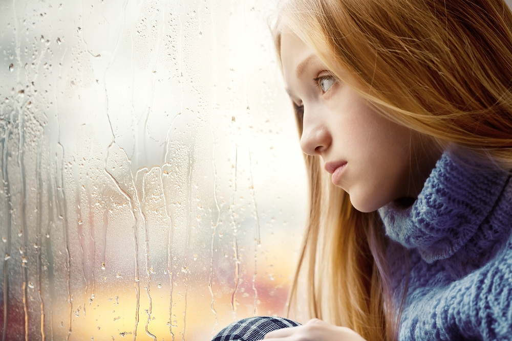 Teen girl depressed looking out window. Represents need for trauma therapy for teens in katy, tx. Also represents need for trauma counseling for teens in katy, tx 77494.